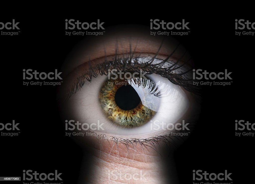 Eye looking through a keyhole in close-up stock photo