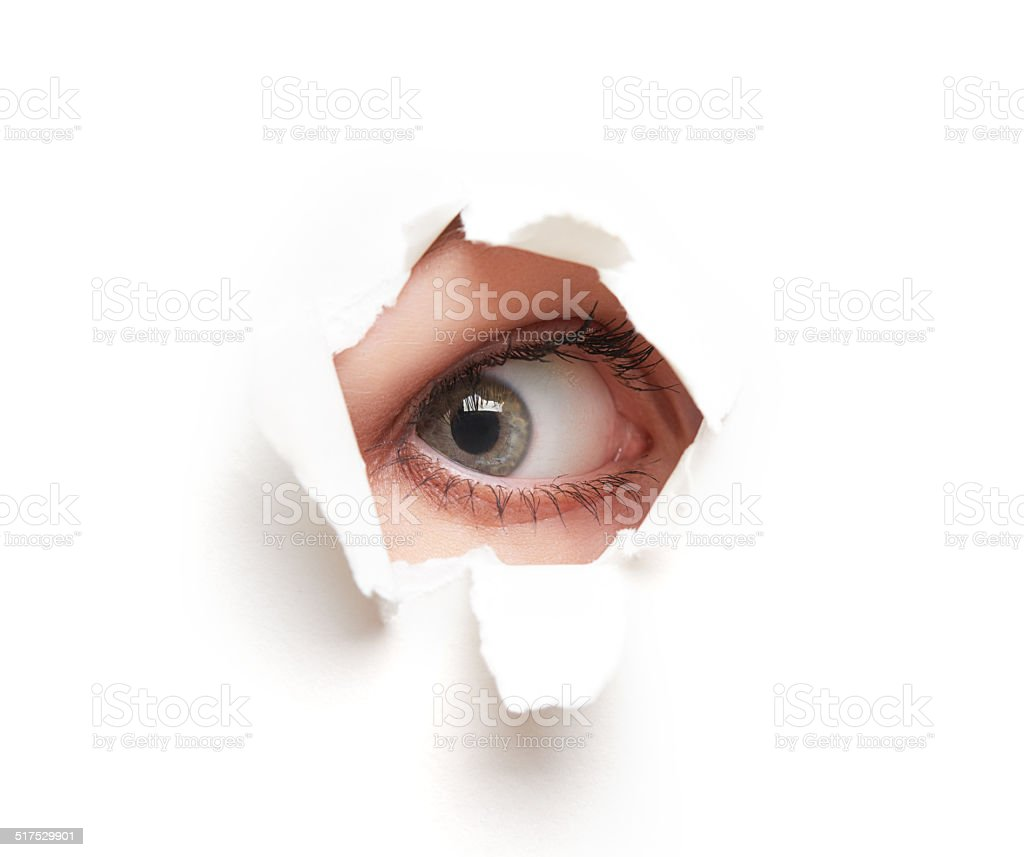 Eye looking through  hole in  white empty paper poster stock photo