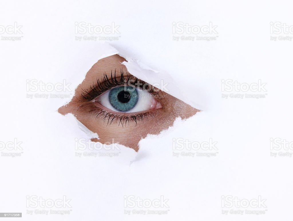 Eye looking through hole stock photo