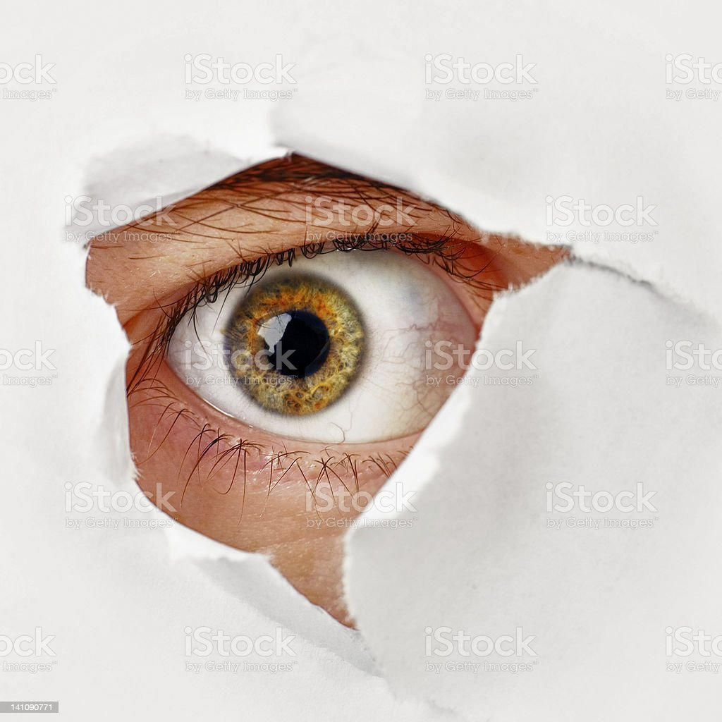 Eye looks through a hole in the paper - spy stock photo
