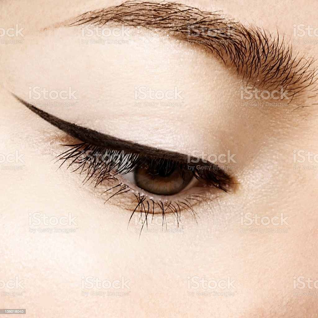 eye makeup with precise black eyeliner line looking down stock photo