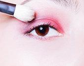 Eye makeup. Woman applying pink eyeshadow powder