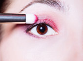 Eye makeup. Woman applying pink eyeshadow powder