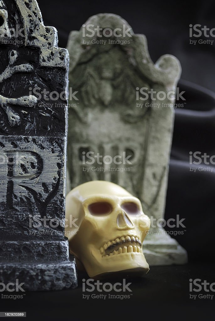 Eye Sockets of Spooky Halloween Skull Glow Red with Tombstones stock photo