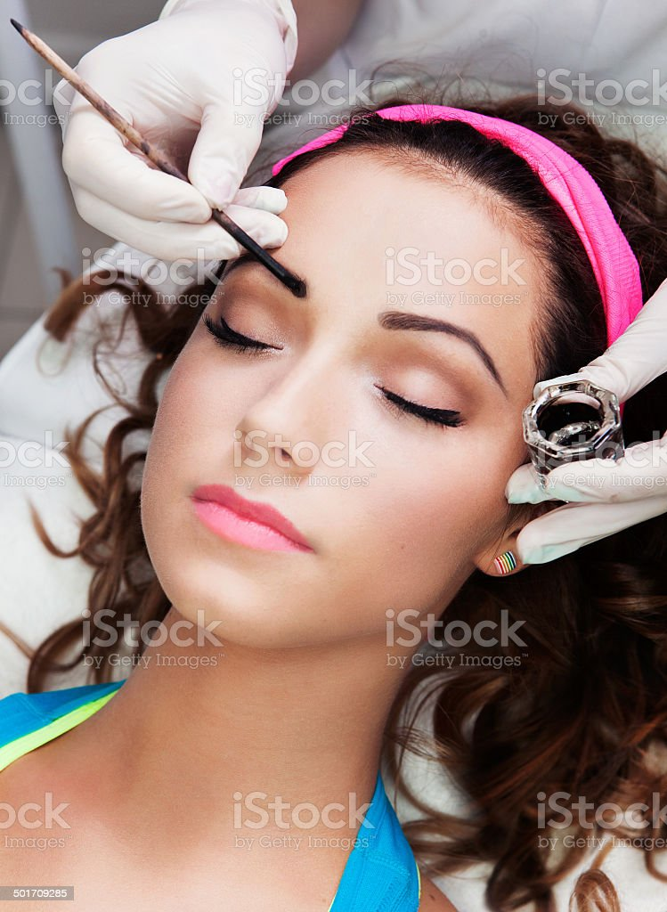 Eyebrows tinting treatment with natural henna dye stock photo