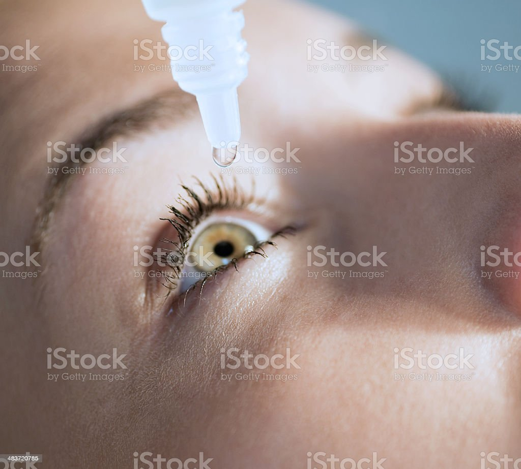 Eyedropper releasing fluid into an eye stock photo