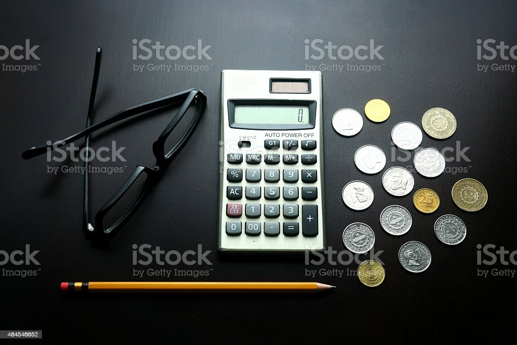 Eyeglass, calculator, coins and pencil on a wooden table stock photo