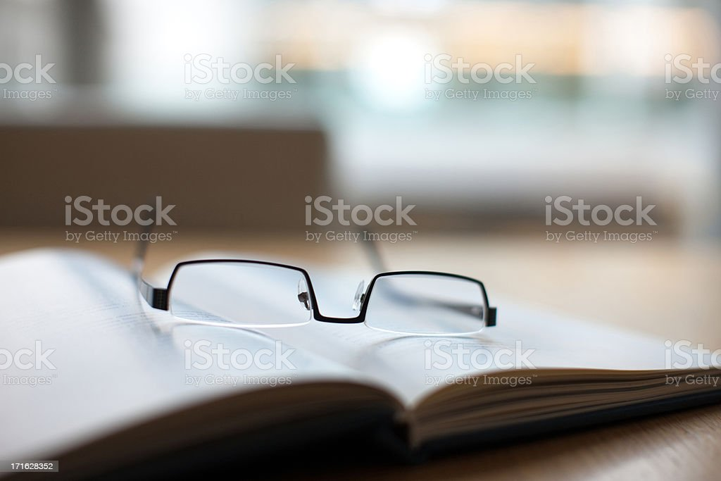 Eyeglasses and book on conference table stock photo