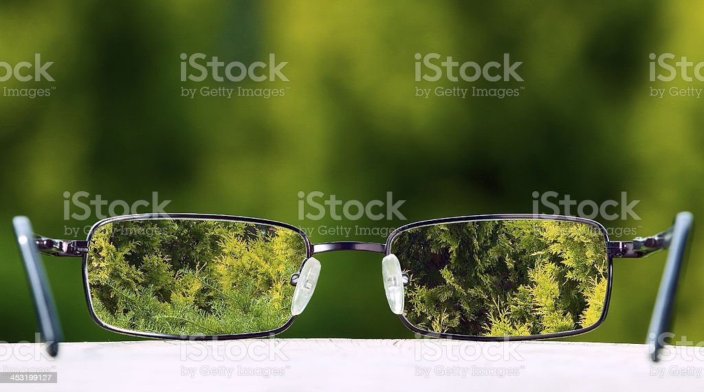 Eyeglasses bringing focus to a green nature background royalty-free stock photo