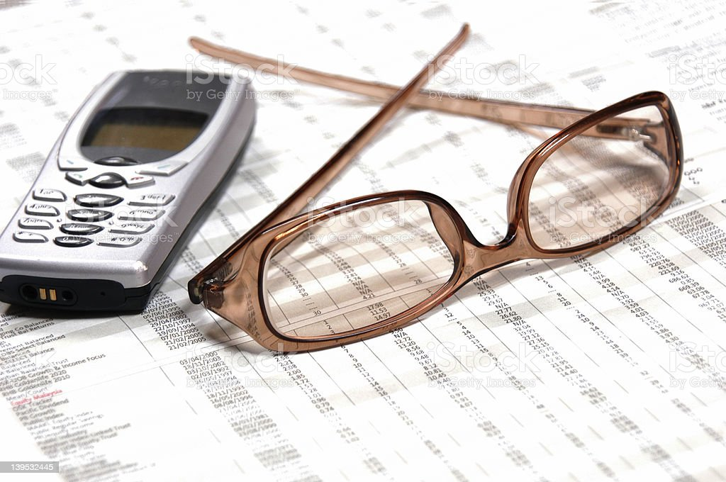 Eyeglasses & Cellphone on financial newspaper stock photo