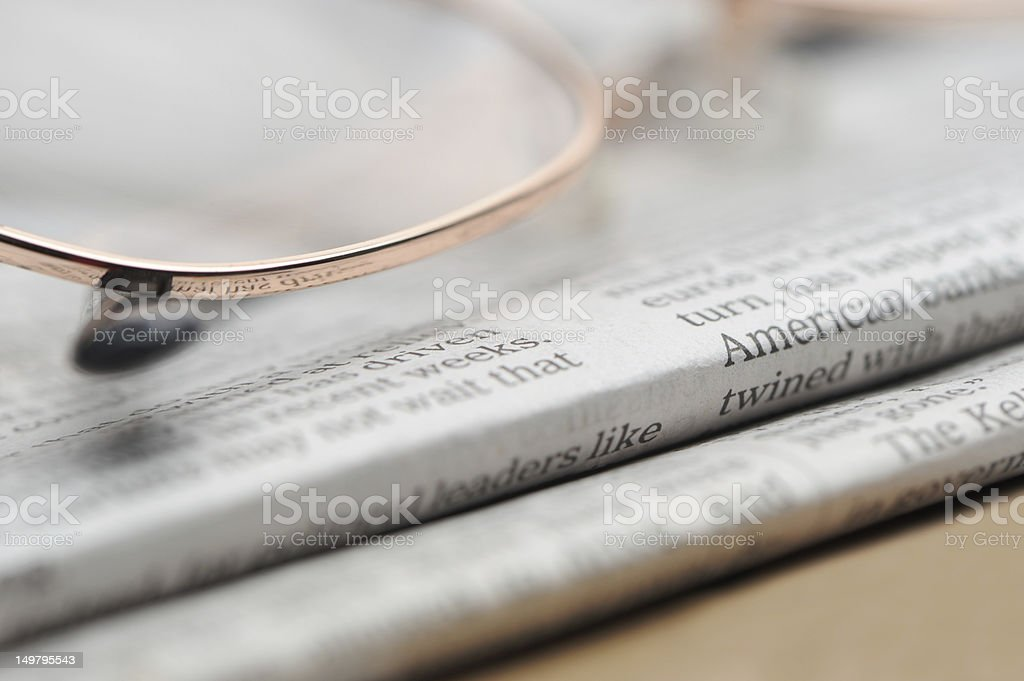 Eyeglasses lie on a pile of newspapers royalty-free stock photo
