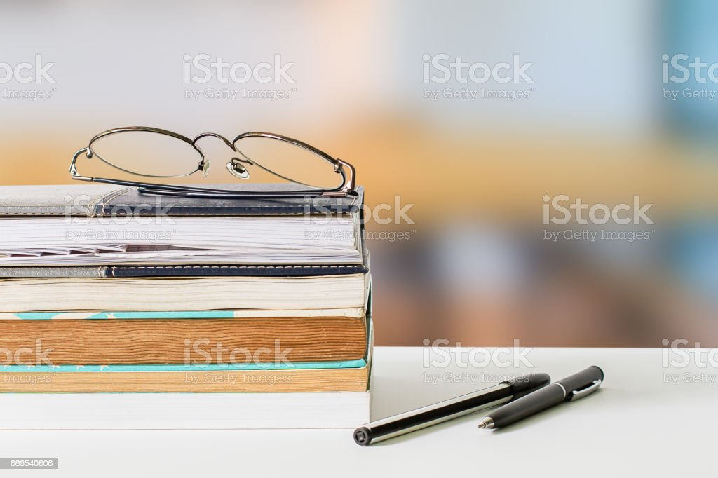 Eyeglasses on books and pens on white table on blurred library background stock photo