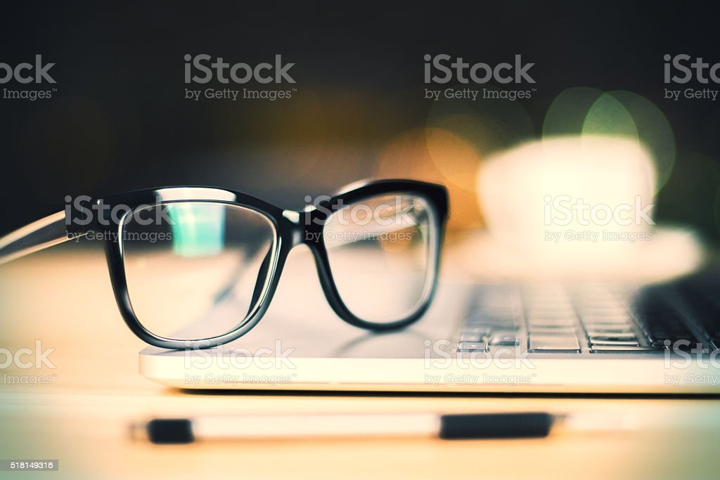 Eyeglasses on laptop with pen on wooden table, close up stock photo