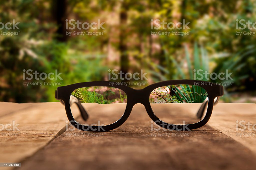 Eyeglasses on rustic wooden table. Forest background. stock photo