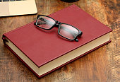 EyeGlasses on top of Red Book wooden table