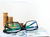 Eyeglasses with US bills and coins on desk