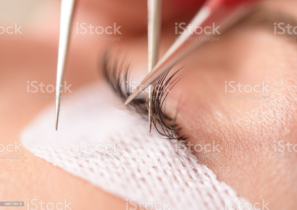 Eyelash application with tweezers stock photo