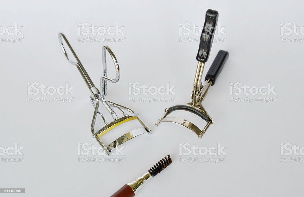 eyelash curler and mascara brush on white background stock photo
