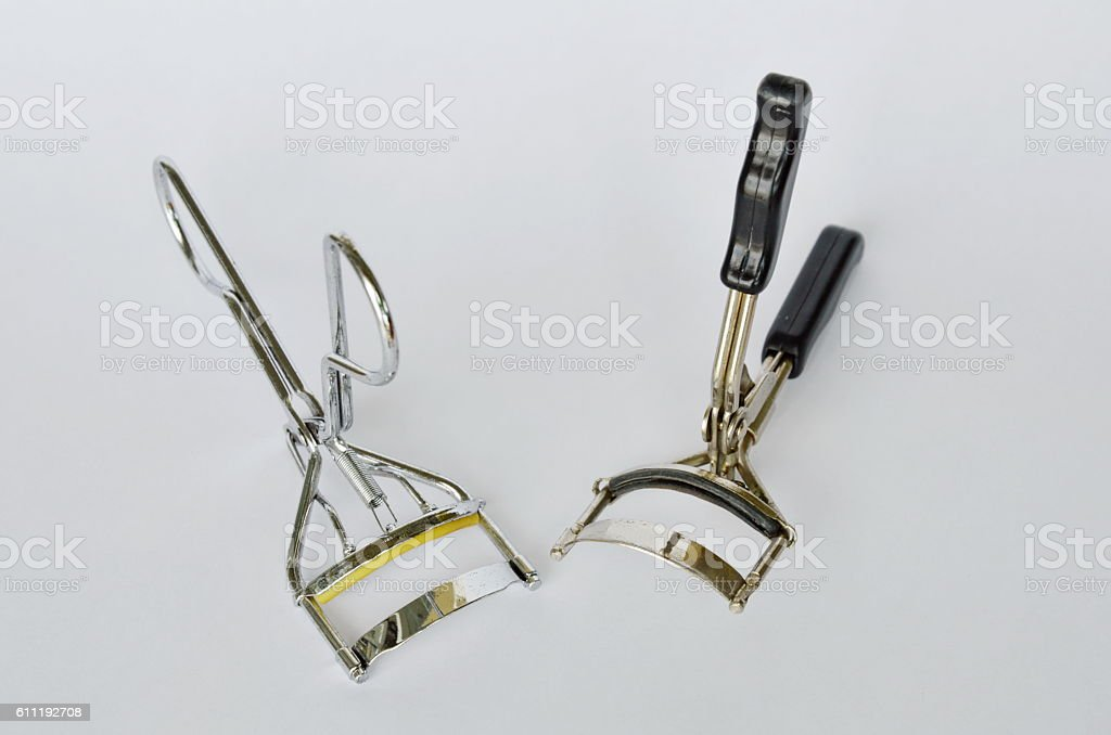 eyelash curler with silver and black handle on white background stock photo