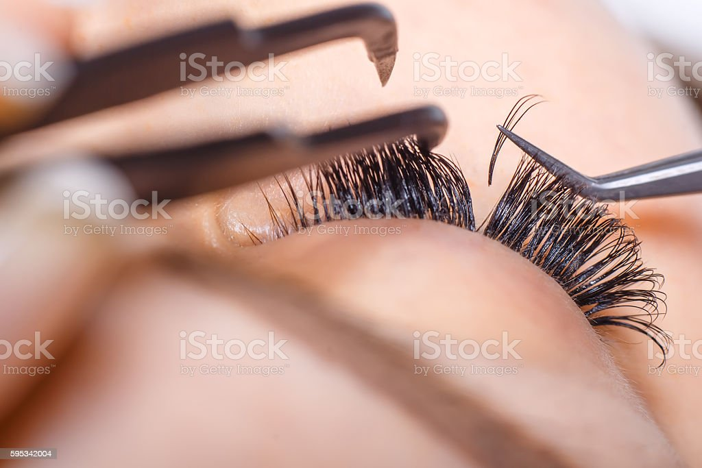 Eyelash Extension Procedure. Woman Eye with Long Eyelashes. Lashes. stock photo