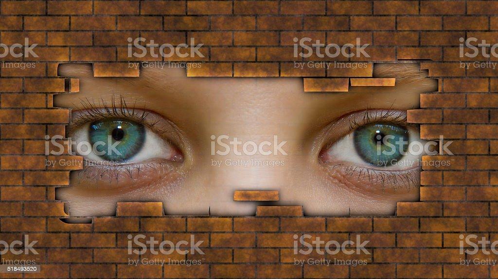 Eyes behind a wall stock photo