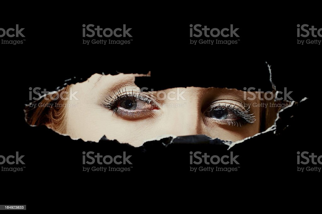Eyes of a young woman peeping through hole stock photo