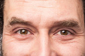 Eyes of white Caucasian man, closeup portrait, Happy