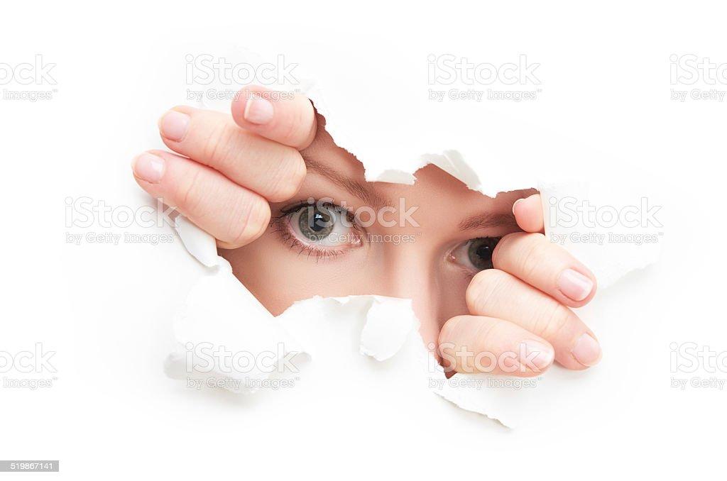 eyes of woman peeking through  hole torn in white paper stock photo