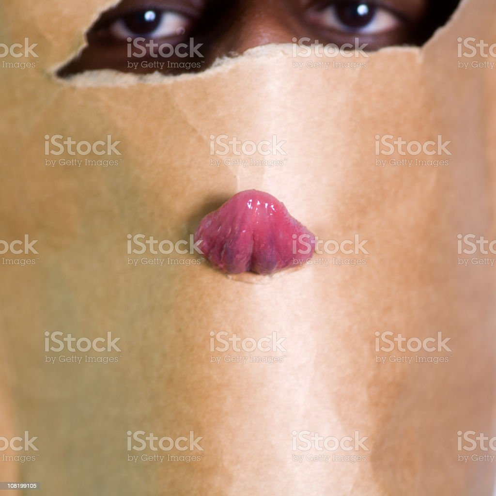 Eyes with Tongue Poking Through Brown Paper Bag stock photo