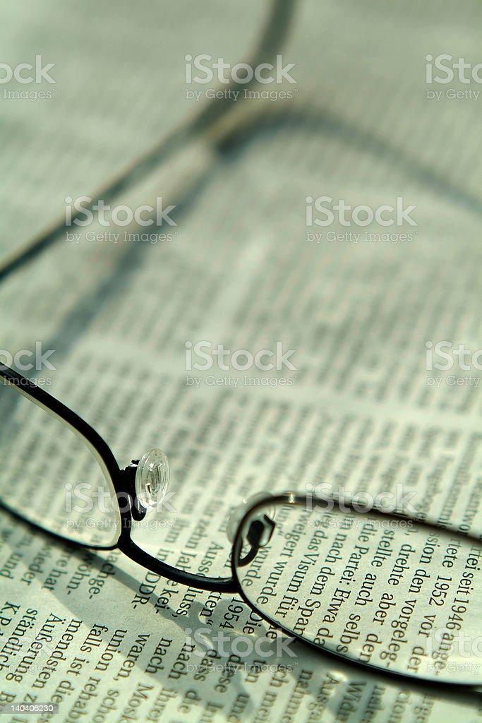 Eyglasses lying on newspaper stock photo