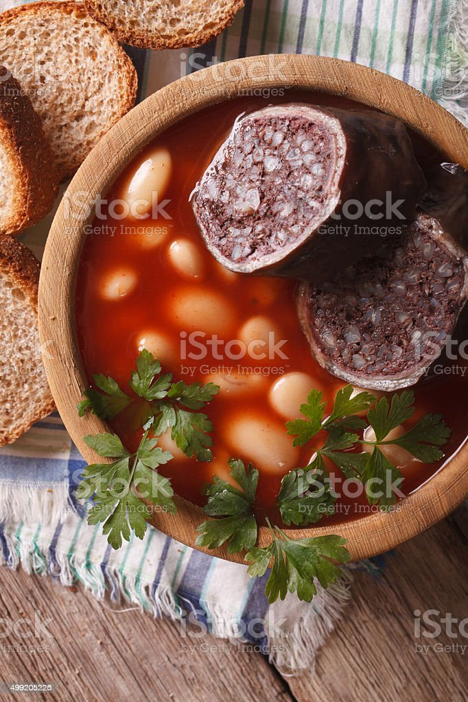 Fabada asturiana closeup in a wooden bowl. vertical top view stock photo