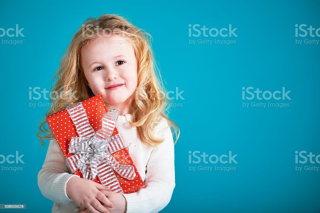 Fabulous little girl carrying gifts on a turquoise background. stock photo