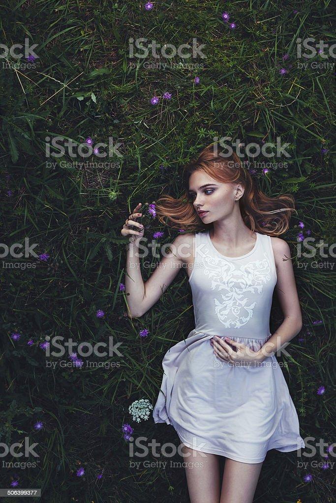 fabulous portrait woman lying down in field with flowers stock photo