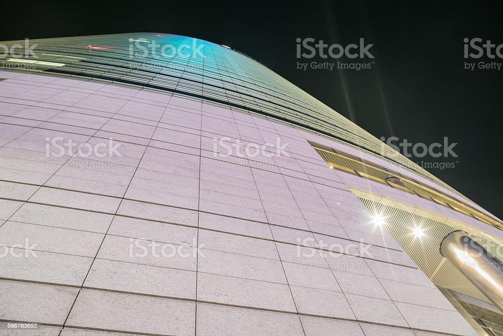 Facade of a futuristic skyscraper by night stock photo