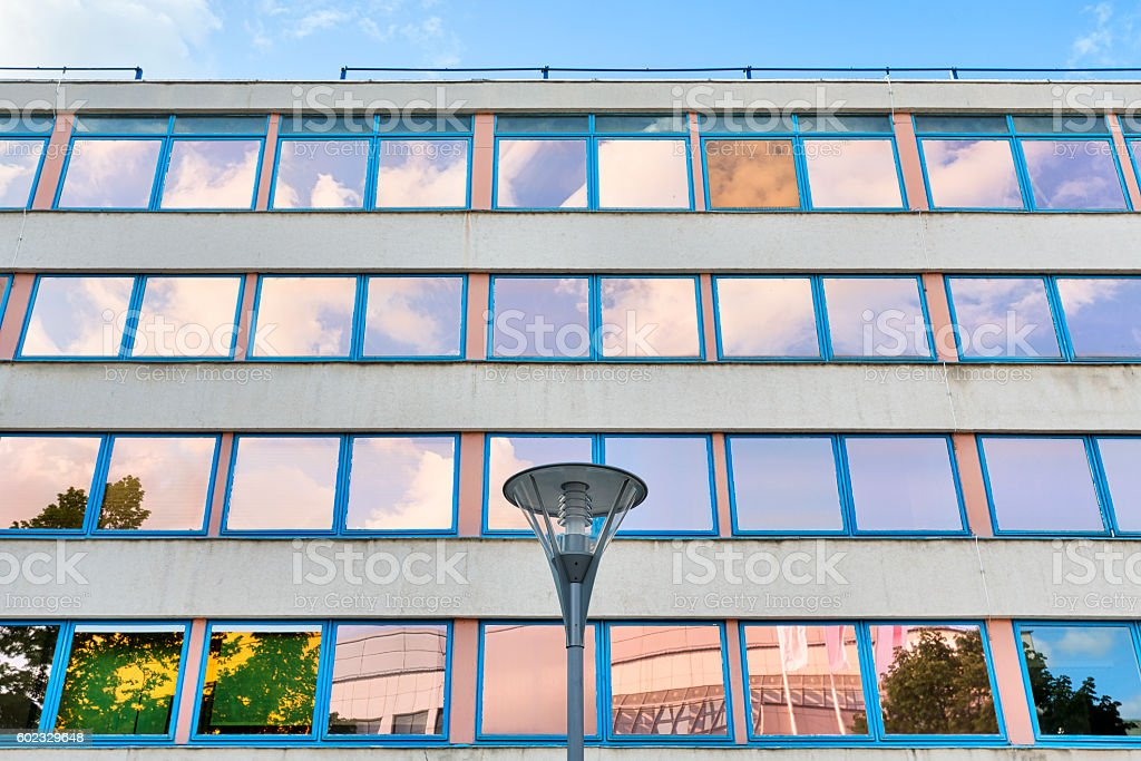 facade of an office building with orange and blue windows stock photo