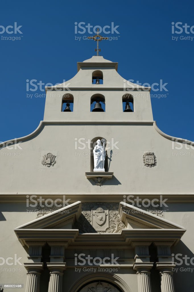 Facade of Cathedral Basilica of St. Augustine in St Augustine, Florida. Broken pediment and doric columns, mix of Neoclassical and Spanish Mission architecture. Bell tower, statue of St Augustine. stock photo