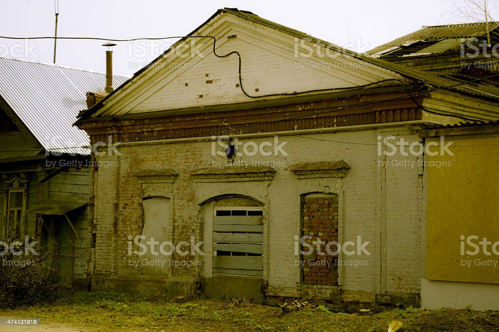 Facade of the destroyed building with boarded up windows a stock photo