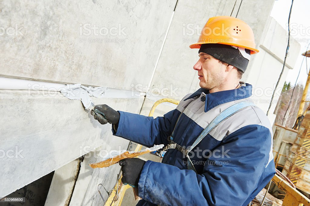 Facade plasterer sealing joint of building wall with putty mastic stock photo