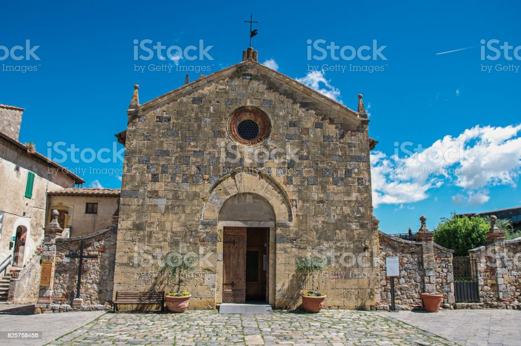 Facade view of an old church in a sunny day at the hamlet of Monteriggioni. stock photo