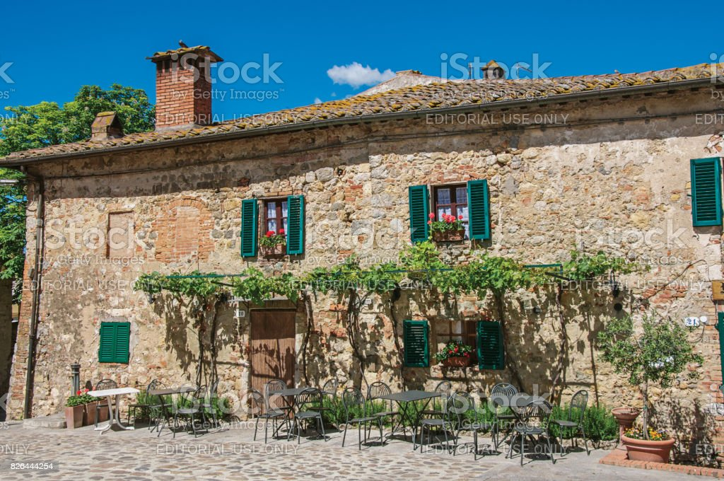 Facade view of an old house with creepers in the hamlet of Monteriggioni. stock photo