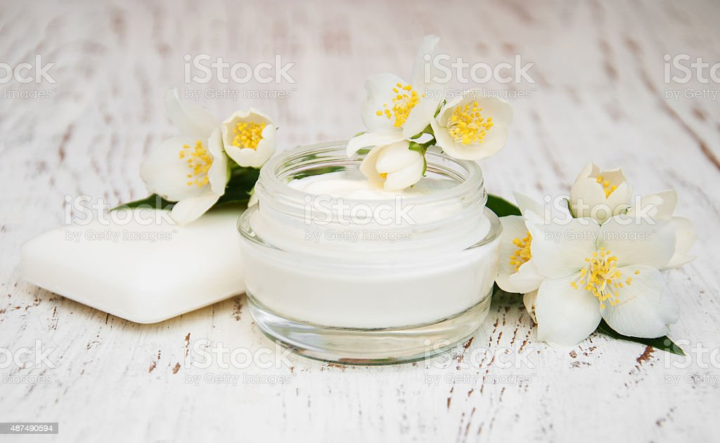 face and body cream moisturizers with jasmine flowers stock photo