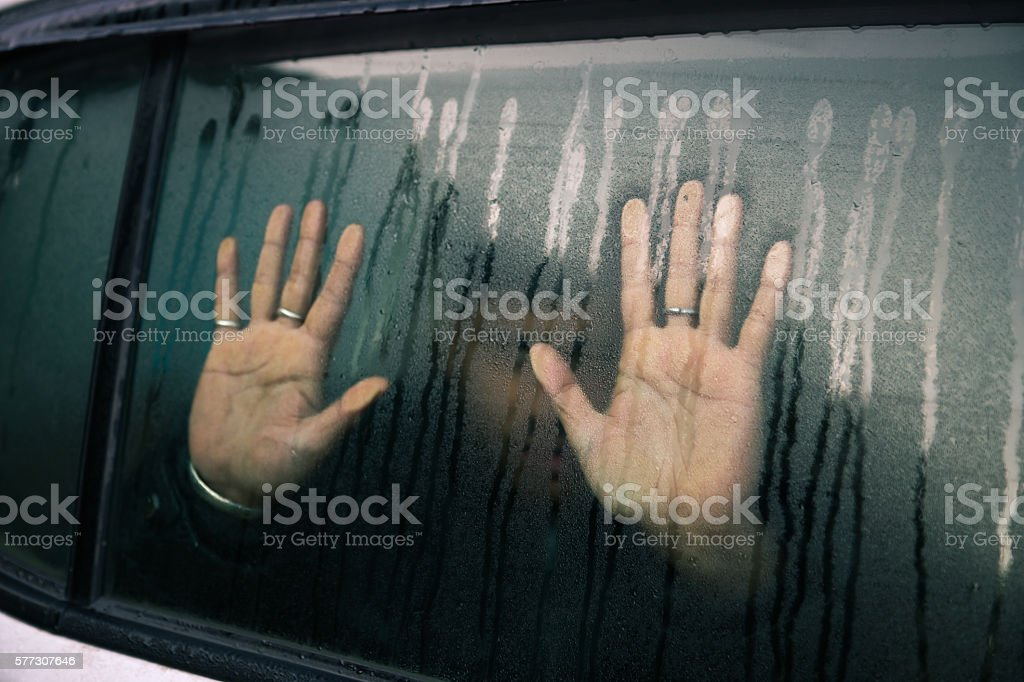 Face behind wet car window stock photo