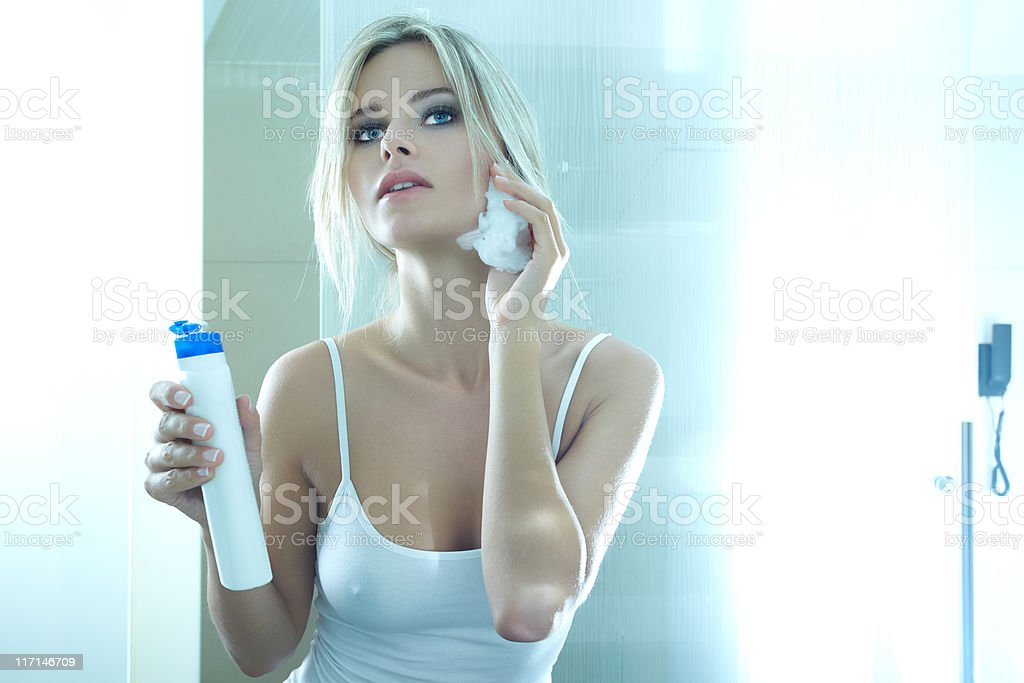 Face cleaning - applying moisturizer stock photo