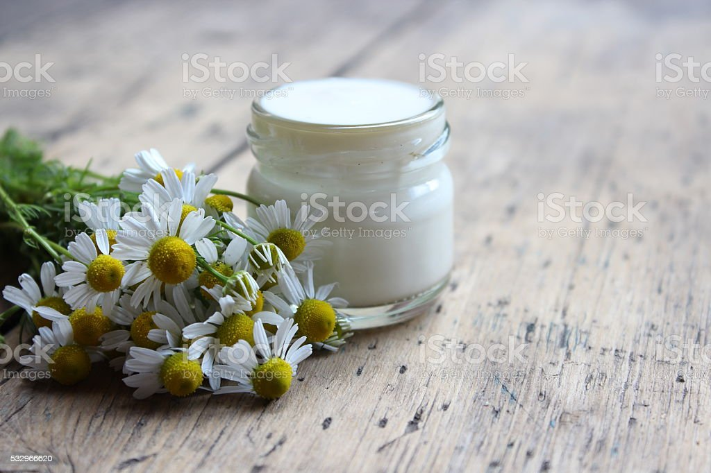 Face cream with flowers of chamomile.Cosmetics. stock photo