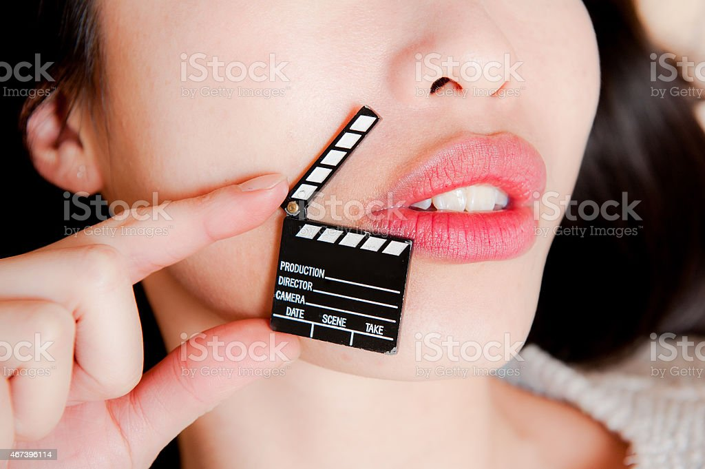 Face detail of sensual woman lips with little clapper board stock photo