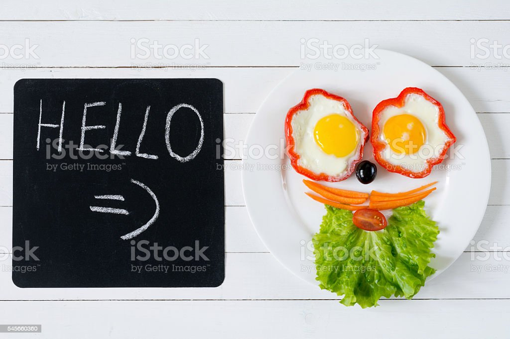 Face made of vegetables, salad and eggs on plate stock photo