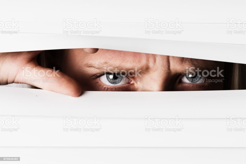 Face obscured, little girl frowns through venetian blinds stock photo