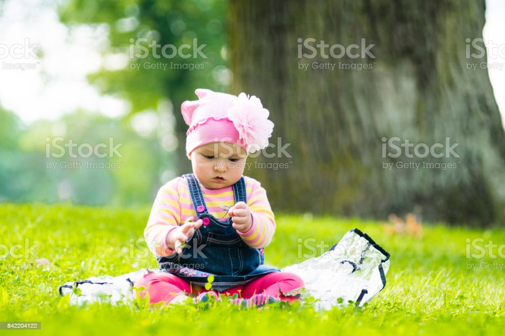 face of a happy beautiful baby girl on nature summer. Sitting on a green grass on sunny day stock photo