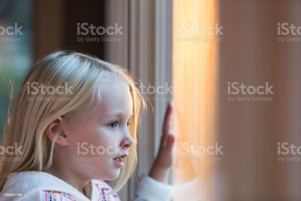 Face of a little girl looking through a window stock photo