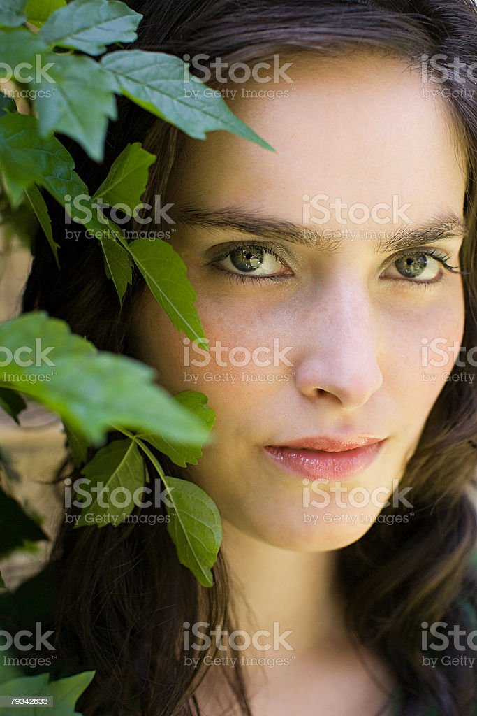 Face of a young woman with leaves stock photo